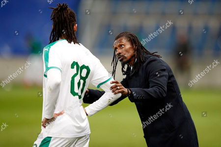 Senegal's head coach Aliou Cisse, right, speaks with Senegal's Armand Traore during a friendly soccer match between Senegal and Bosnia and Herzegovina at the Oceane stadium in Le Havre, northern France