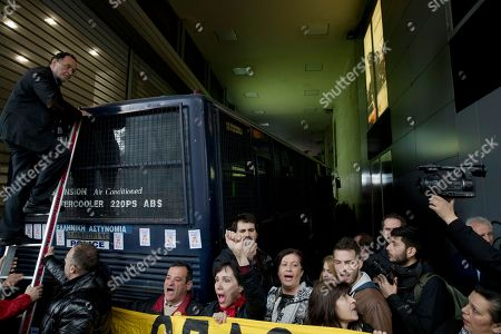 Stock Photo of Panagiotis Lafazanis, former Greek energy minister stands on a ladder as a police vehicle blocks the entrance outside a notary-public's office in Athens on . A few dozen people took part in the protest, as Greek police guard the building. Protesters were opposing the auction of foreclosed properties, a key demand of Greece's bailout creditors