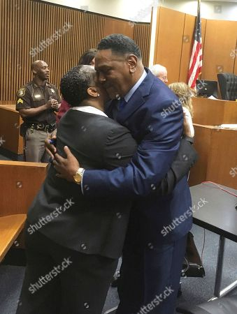Richard Phillips, right, hugs Det. Patricia Little in a Wayne County, Mich., courtroom, in Detroit. Phillips, a Michigan man whose murder conviction was thrown out after he spent 45 years in prison will not face a second trial