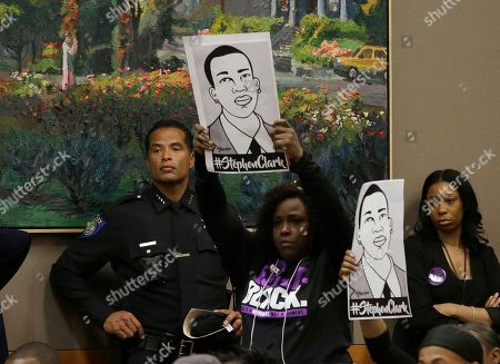 Drawings of police shooting victim Stephon Clark are held up next to Sacramento Police Chief Daniel Hahn, left, during a meeting of the Sacramento City Council held to discuss the shooting, in Sacramento, Calif. Stephon Clark, who was unarmed, was shot and killed by Sacramento Police Officers, Sunday, March 18, 2018