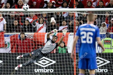 Peru goalkeeper Carlos Caceda dives for a shot from Iceland during the first half of an international friendly soccer match, in Harrison, N.J