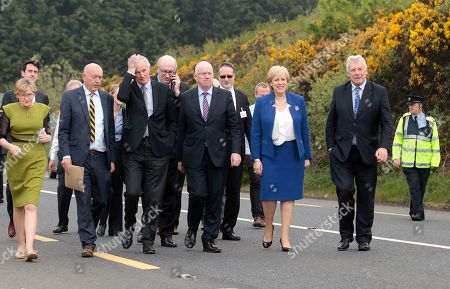 European Union chief Brexit negotiator Michel Barnier, third left, and Irish Minister for Foreign Affairs Charles Flanagan, center, walk along the Irish border close to Castleblayney, Ireland. Thursday March 29, 2018, marks 365 days until Britain leaves the European Union, ending a 46-year marriage that has entwined the economies, legal systems and peoples of Britain and 27 other European nations