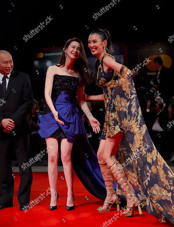 """Qi Wei, Tao Okamoto, John Woo. Director John Woo looks at actresses Qi Wei, left, and Tao Okamoto posing for photographers at the premiere for the film """"Zhuibu"""" (Manhunt) at the 74th edition of the Venice Film Festival in Venice, Italy"""
