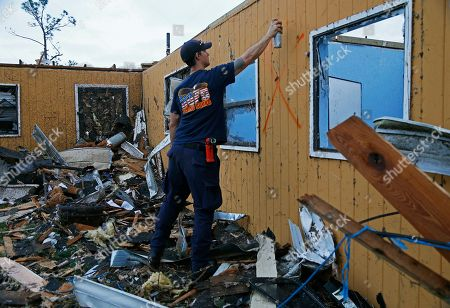New Orleans Firefighter Jared Carter spray paints a search signal after conducting a secondary search of homes damaged by a tornado that touched down yesterday in eastern New Orleans, . Officials say tornadoes that struck in southeastern Louisiana destroyed homes and businesses, flipped vehicles and left thousands without power