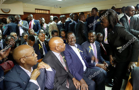 Opposition leader Raila Odinga, centre, waits for the judgement at the Mililani low court in Nairobi, in Nairobi, Kenya . A Kenyan judge has fined the country's interior minister, police chief and permanent secretary for immigration $2,000 each for contempt of court over the deportation of an opposition politician, Miguna Miguna