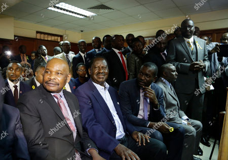 Opposition leader Raila Odinga, centre, listens to the judgement at the Mililani low court in Nairobi, in Nairobi, Kenya . A Kenyan judge has fined the country's interior minister, police chief and permanent secretary for immigration $2,000 each for contempt of court over the deportation of an opposition politician, Miguna Miguna