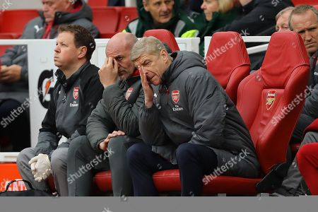 Manager of Arsenal, Arsene Wenger and his assistant, Steve Bould hide their faces in frustration