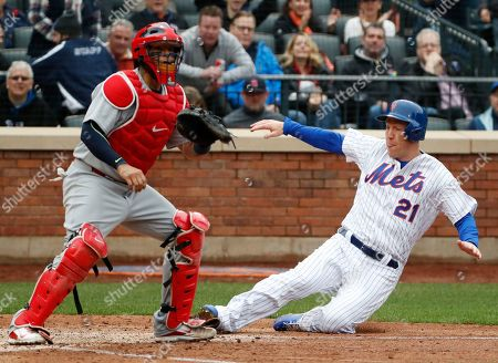 Stock Picture of Yadier Molina, Todd Frazier. New York Mets' Todd Frazier (21) scores ahead of the throw to St. Louis Cardinals catcher Yadier Molina (4) on Adrian Gonzalez's double in the fifth inning of an opening day baseball game, in New York