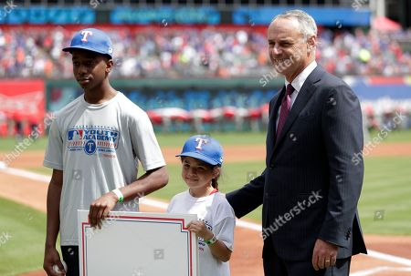 Texas Rangers MLB Youth Academy participants Benjamin King, left, and Aubrey Robledo, center, pose with baseball commissioner Rob Manfred, right, before the start of an opening day baseball game between the Houston Astros and Texas Rangers in Arlington, Texas
