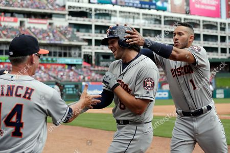 AJ Hinch, Carlos Correa, Jake Marisnick. Houston Astros' AJ Hinch (14) and Carlos Correa (1) congratulate Jake Marisnick, center, on his solo home run that came off of Texas Rangers starter Cole Hamels int he fourth inning of a baseball game in Arlington, Texas