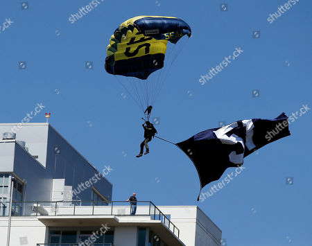 Former Seal team member Jim Woods glides down in a parachute with the number 51 flag to honor former San Diego Padres Trevor Hoffman during opening day ceremonies before a baseball game against the Milwaukee Brewers in San Diego