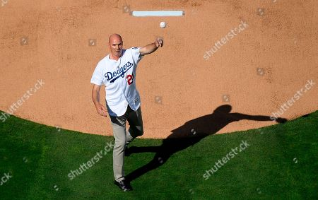 Former Los Angeles Dodgers' Kirk Gibson throws out the ceremonial first pitch prior to an opening day baseball game between the Dodgers and the San Francisco Giants, in Los Angeles
