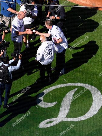 Orel Hershiser, Kirk Gibson, Tommy Lasorda. Former Los Angeles Dodgers pitcher Orel Hershiser, upper right, hands a ball to former Dodger Kirk Gibson, upper left, as former manager Tommy Lasorda (2) watches before Gibson threw out the ceremonial first pitch prior to an opening day baseball game against the San Francisco Giants, in Los Angeles