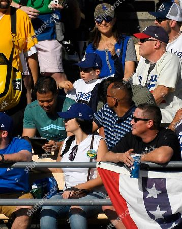 Jake Henderson, 8, second from top, watches from the specially designated Kirk Gibson seat in the right field pavilion during an opening day baseball game between the Los Angeles Dodgers and the San Francisco Giants, in Los Angeles. The 8-year-old, from Los Angeles, was the first person to sit in the seat that was designated to commemorate Gibson's historic pinch-hit, walkoff home run in Game 1 of the 1988 World Series. The Dodgers painted the seat where his ball landed blue