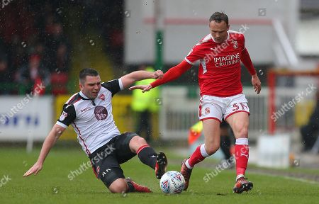 Matthew Taylor  of Swindon is tackled by  Alex Kenyon of Morecambe