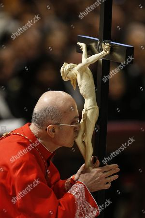 Stock Picture of Cardinal Tarcisio Bertone kisses the Crucifix during the Lord's Passion on Good Friday at Saint Peter's Basilica, Vatican City, 30 March 2018. Good Friday is a Christian holiday commemorating the crucifixion of Jesus Christ and his death at Calvary. It is observed during Holy Week as part of the Easter Triduum on the Friday preceding Easter Sunday.