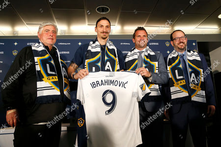 LA Galaxy's head coach Sigi Schmid, left, the Galaxy's newest player Zlatan Ibrahimovic of Sweden, team president Chris Klein and AEG president and CEO Dan Beckerman, pose with Ibrahimovic's new jersey during an MLS soccer press conference following a training session at the StubHub Center, in Carson, Calif