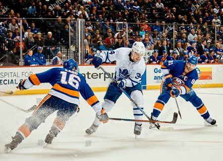 Auston Matthews, Andrew Ladd, John Tavares. Toronto Maple Leafs' Auston Matthews, center, battles for the puck with New York Islanders' John Tavares, right, and Andrew Ladd, left, during the second period of an NHL hockey game, in New York