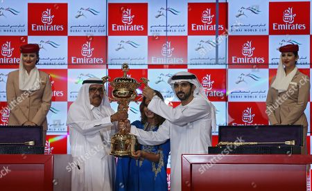 Stock Image of Sheikh Hamdan bin Mohammed bin Rashid Al Maktoum (R)Crown Prince of Dubai receives the winner's trophy from  Sheikh Hamdan bin Rashid Al Maktoum (L), Deputy Ruler of Dubai and the Minister of Finance and Industry of the United Arab Emirates after the main race of the Dubai World Cup 2018 at the Meydan race course in Gulf emirate of Dubai, United Arab Emirates, 31 March 2018. The Dubai World Cup is one of the richest events in the horse racing sporting calendar with 30 million US dollars in prize money.