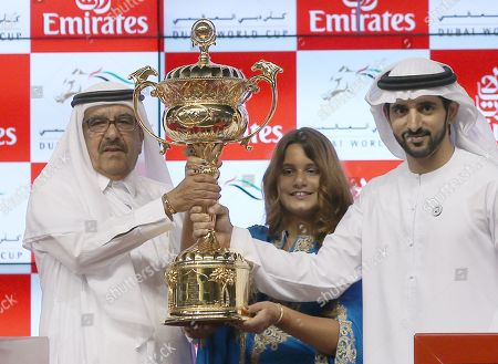 Stock Picture of Sheikh Mohammed bin Rashid Al Maktoum, (R) the Vice President and Prime Minister of the United Arab Emirates, and ruler of the Emirate of Dubai dances while Sheikh Hamdan bin Mohammed bin Rashid Al Maktoum(C)Crown Prince of Dubai receive the winner's trophy from   Sheikh Hamdan bin Rashid Al Maktoum (L), Deputy Ruler of Dubai and the Minister of Finance and Industry of the United Arab Emirates after the main race of the Dubai World Cup 2018 at the Meydan race course in Gulf emirate of Dubai, United Arab Emirates, 31 March 2018. The Dubai World Cup is one of the richest events in the horse racing sporting calendar with 30 million US dollars in prize money.