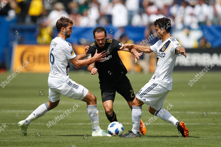 Marco Urena, Jorgen Skjelvik, Servando Carrasco. Los Angeles FC's Marco Urena, center, is defended by Los Angeles Galaxy's Jorgen Skjelvik, left, of Norway, and Servando Carrasco during the first half of an MLS soccer match, in Carson, Calif
