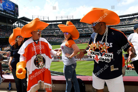 David Arriasola, Michelle Feagins, and Carlos Campos; left to right; Astros fans who call themselves the Big Hat Posse, joke around before a baseball game between the Texas Rangers and the Houston Astros, in Arlington, Texas