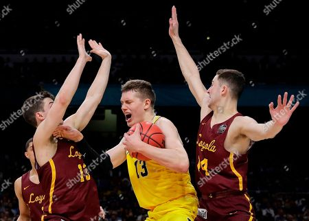 Michigan's Moritz Wagner (13) battles for the ball against Loyola-Chicago's Clayton Custer (13) and Ben Richardson (14) during the first half in the semifinals of the Final Four NCAA college basketball tournament, in San Antonio