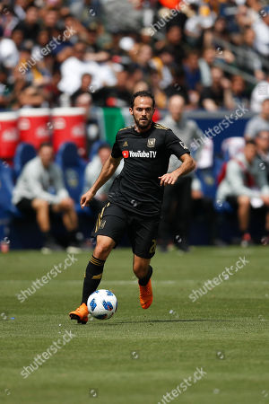 Los Angeles FC's Marco Urena dribbles the ball during the first half of an MLS soccer match against the Los Angeles Galaxy, in Carson, Calif