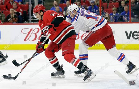 Stock Image of Trevor van Riemsdyk, Kevin Hayes. New York Rangers' Kevin Hayes (13) and Carolina Hurricanes' Trevor van Riemsdyk (57) chase the puck during the first period of an NHL hockey game in Raleigh, N.C
