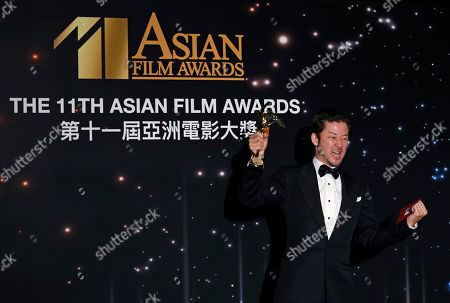 Japanese actor Tadanobu Asano poses after winning the Best Actor Award of the Asian Film Awards in Hong Kong