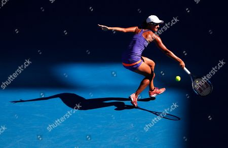 Australia's Arina Rodionova casts her shadow on the court as she chases down a return to Denmark's Caroline Wozniacki during their first round match at the Australian Open tennis championships in Melbourne, Australia