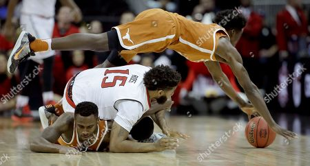 Texas' Andrew Jones leaps over teammate Kendal Yancy and Texas Tech's Aaron Ross (15) to retrieve a loose ball during the second half of an NCAA college basketball game in the Big 12 tournament, in Kansas City, Mo. Texas won 61-52