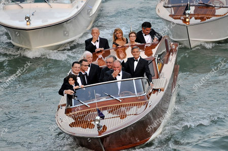 Stock Photo of George Clooney, Ramzi Alamuddin, Nick Clooney, Nina Bruce. Actor George Clooney, right, waves from a boat with Ramzi Alamuddin, third from right front row, father of her fiancee Amal Alamuddin, his father Nick Clooney, fourth from right front row, and his mother Nina Bruce, second from right back row on their way to the Aman hotel ahead of his wedding in Venice, Italy