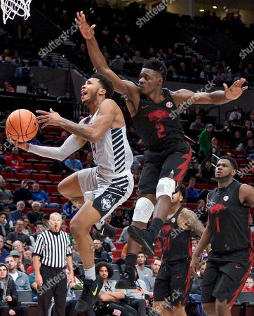 Jalen Adams, Adrio Bailey. Connecticut guard Jalen Adams, left, shoots past Arkansas forward Adrio Bailey (2) during the first half of an NCAA college basketball game in the Phil Knight Invitational tournament in Portland, Ore