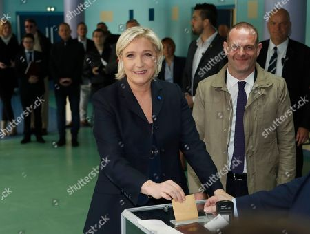 Far-right leader and candidate for the 2017 French presidential election Marine Le Pen casts her vote for the first-round presidential election, while National Front Henin-Beaumont's mayor Steeve Briois, right, looks, in Henin-Beaumont, northern France, . French voters are casting ballots for their next president in an unusually close first-round election Sunday, after a campaign dominated by concerns about jobs and immigration and clouded by security fears following a recent attack on police guarding the Champs-Elysees in Paris