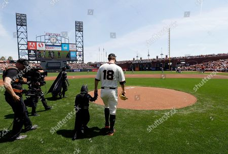 Stock Picture of Miles Scott, second from right, dressed as Batkid, walks to the mound with San Francisco Giants pitcher Matt Cain (18) to throw the ceremonial first pitch before a home opener baseball game between the Giants and the Arizona Diamondbacks in San Francisco, . On Nov. 15, 2013, Scott, a Northern California boy with leukemia, fought villains and rescued a damsel in distress as a caped crusader through The Greater Bay Area Make-A-Wish Foundation