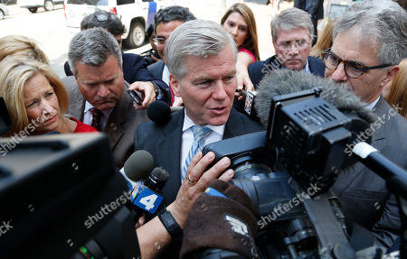 Former Virginia Gov. Bob McDonnell, center, answers reporters questions as he leaves the 4th U.S. Circuit Court of Appeals after a hearing on the appeal of his corruption conviction in Richmond, Va., . McDonnell and his wife, Maureen, were convicted of taking more than $165,000 in gifts and loans from a wealthy businessman in exchange for promoting his company's dietary supplements. The former governor was sentenced to two years in prison, his wife to one year and one day