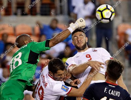 Patrick Pemberton, Lucas Cavallini. Costa Rica goalkeeper Patrick Pemberton (18) makes a save against Canada forward Lucas Cavallini (9) in the second half of a CONCACAF Gold Cup soccer match in Houston