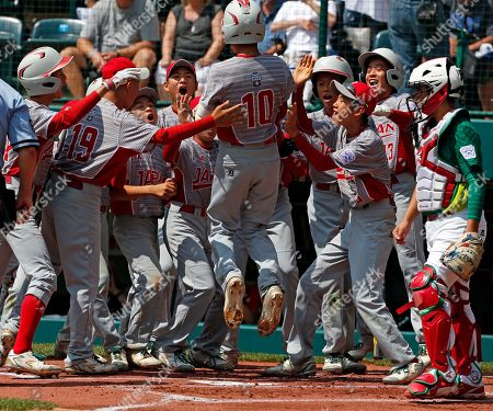 Japan's Keitaro Miyahara (10) is greeted by teammates after hitting a solo home run off Mexico pitcher Jorge Garcia in the first inning of the International Championship baseball game at the Little League World Series tournament, in South Williamsport, Pa