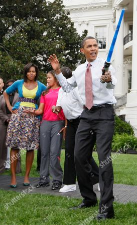 Barack Obama, Michelle Obama, April Holmes. President Barack Obama wields a plastic saber as first lady Michelle Obama, rear left, and Track and Field paralympian April Holmes, second left, watch a fencing demonstration on the South Lawn of the White House in Washington, during an event supporting Chicago's 2016 Olympic bid