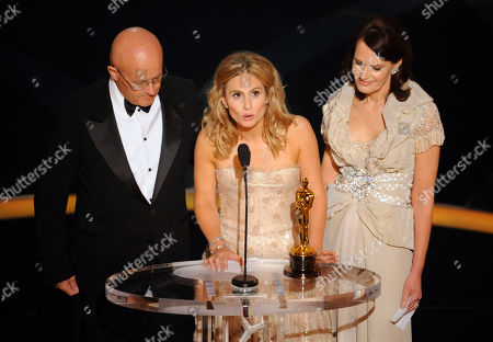 """Kate Ledger, Kim Ledger, Sally Bell. Sister Kate Ledger looks up to her brother, Heath Ledger, after accepting the Oscar for best supporting actor on his behalf who won for his work in """"The Dark Knight"""" during the 81st Academy Awards, in the Hollywood section of Los Angeles. Looking on are Heath's father, Kim Ledger, left, and mother, Sally Bell"""