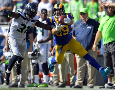 Seattle Seahawks strong safety Kam Chancellor, left, breaks up a pass intended for Los Angeles Rams tight end Tyler Higbee during the first half of an NFL football game, in Los Angeles
