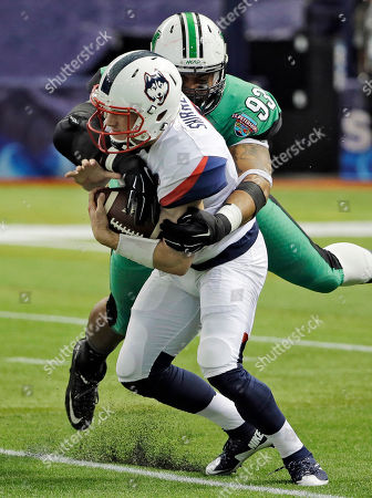Stock Image of Bryant Shirreffs, Steve Dillon. Connecticut quarterback Bryant Shirreffs (4) is sacked by Marshall defensive lineman Steve Dillon (93) during the first quarter of the St. Petersburg Bowl NCAA college football game, in St. Petersburg, Fla