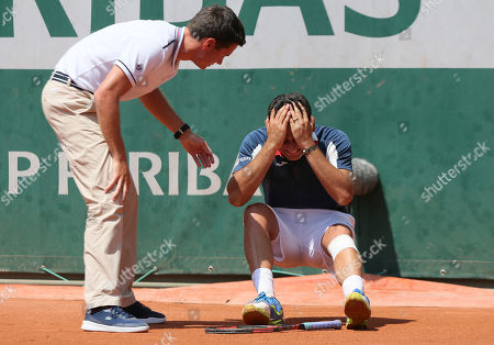 Stock Photo of An official tends to Spain's Nicolas Almagro as he collapses with a left knee injury in his second round match against Argentina's Juan Martin del Potro at the French Open tennis tournament at the Roland Garros stadium, in Paris, France. . Almagro was unable to continue