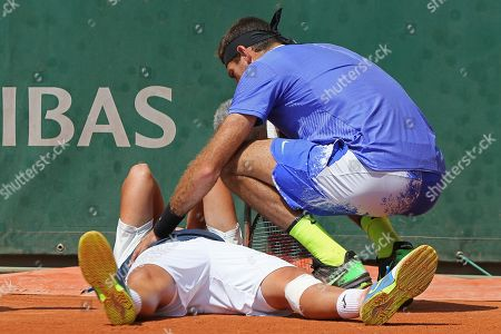 Spain's Nicolas Almagro is comforted by Argentina's Juan Martin del Potro after he collapsed with a left knee injury in his second round match against at the French Open tennis tournament at the Roland Garros stadium, in Paris, France. . Almagro was unable to continue to play
