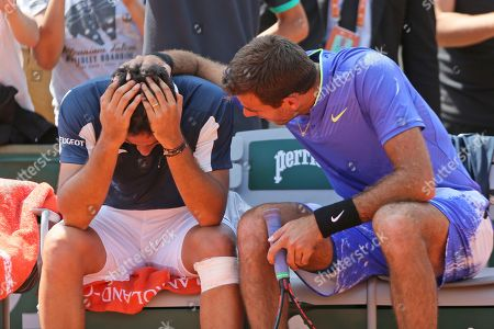 Spain's Nicolas Almagro, left, is comforted by Argentina's Juan Martin del Potro after he collapsed with a left knee injury in his second round match against at the French Open tennis tournament at the Roland Garros stadium, in Paris, France. . Almagro was unable to continue to play