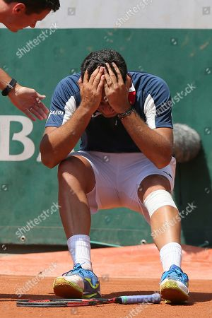 Stock Picture of An official tends to Spain's Nicolas Almagro as he collapses with a left knee injury in his second round match against Argentina's Juan Martin del Potro at the French Open tennis tournament at the Roland Garros stadium, in Paris, France. . Almagro was unable to continue