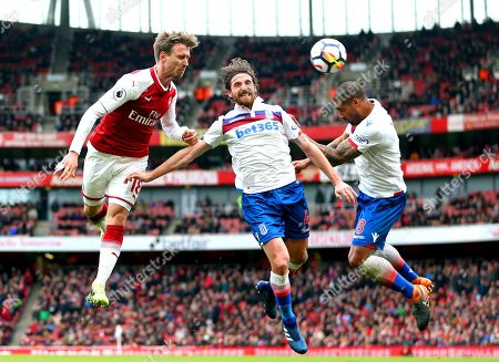 Nacho Monreal of Arsenal heads the ball ahead of Glen Johnson and Joe Allen of Stoke City