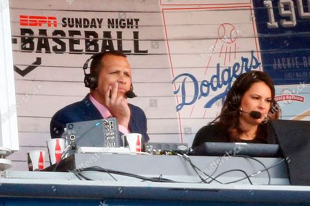 ESPN broadcaster Alex Rodriguez, left, works from the Vin Scully Press Box during the baseball game between the Los Angeles Dodgers and San Francisco Giants, in Los Angeles