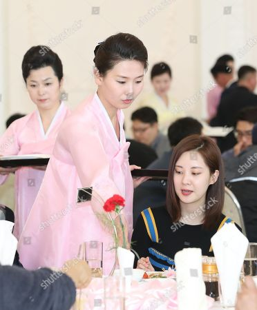A North Korean employee dressed in the 'hanbok' traditional Korean costume, waits on a table for Seohyun (R), a member of a 190-member South Korean art troupe, at Okryukwan Restaurant in Pyongyang, North Korea, 02 April 2018. The group was in the North Korean capital to hold performances on 01 and 03 April.